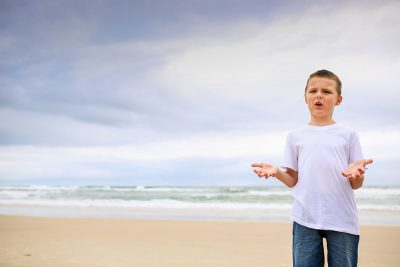 boy-questioning-why-the-family-needs-to-have-an-early-morning-beach-family-photography-session-gold-coast