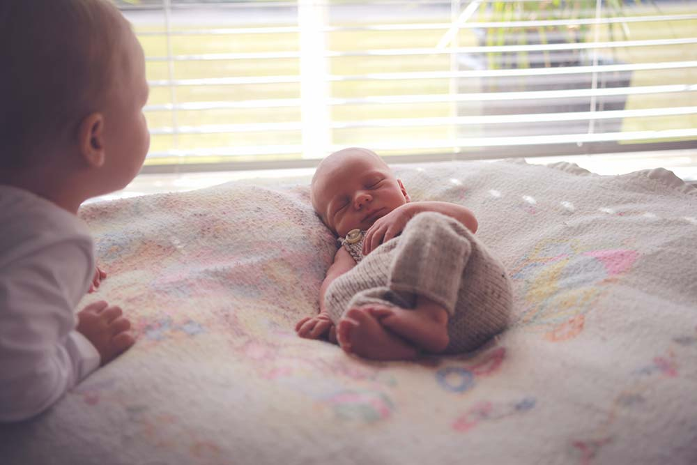 Newborn-Lifestyle-Photographer-big-brother-looking-over-new-baby-brother-gold-coast