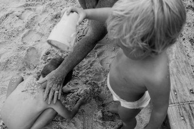 toddler-pouring-a-cup-of-sand-over-his-cousin-Day-in-the-Life-Photography-Storytelling-Gold-Coast-Australia