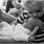 Big-brother-kissing-new-baby-sister-gold-coast-First-Glimpse-newborn-photography