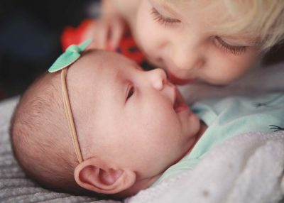 big-brother-giving-kisses-to-new-baby-sister-with-blaze-truck-Newborn-Photography-Lifestyle-Photographer