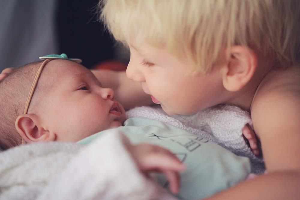 precious-moment-with-big-brother-chatting-with-little-sister-Lifestyle-newborn-photography-gold-coast