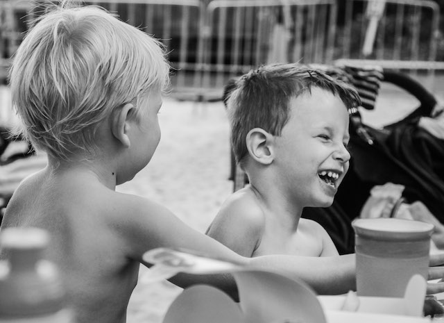 Beautiful-children-in-a-private-joke-moment-at Wet-n-wild-gold-coast-family-documentary-photography