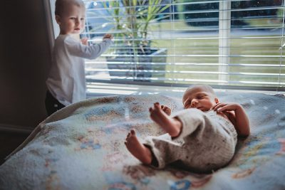 Toddler-looking-out-window-gets-distracted-by-newborn-brother-making-some noises-nearby-gold-coast-in-home-newborn-photography