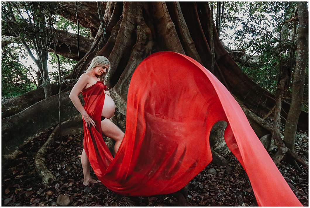 Rainforest-inspired-maternity-photography-with-striking-red-flowing-material-gold-coase-maternity-photography