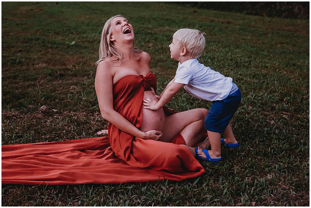 gold-coast-rainforest-maternity-image-with-pregnant-mum-and toddler-giving-bump-kisses