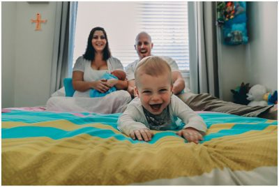Toddler-being-pulled-back-on-bed-in-newborn-at-home-family-photography-session-gold-coast