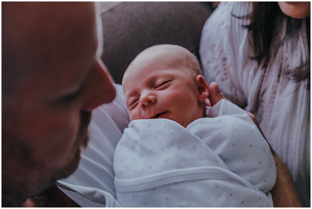 newborn-baby-settling-into-dads-arms-in-newborn-inhome-photography-session-gold-coast