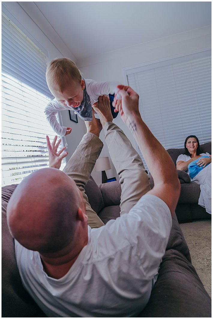 toddler-playing-with-dad-on-the-couch-being-lifted-into-the-air-from-dads-feet-newborn-inhome-photography-gold-coast