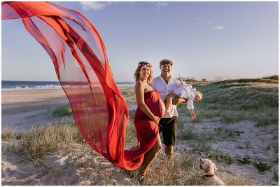 Beautiful-full-bloom-pregnant-woman-with-her-partner-toddler-and-puppy-on-the-sand-dunes-at-the-spit-gold-coast-maternity-photography
