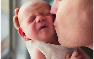 Newborn-getting-dad-kisses-and-reacting-gold-coast-newborn-inhome-photography
