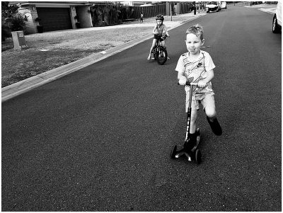 two-kids-riding-a-bike-and-a-scooter-with-concentration-toungue-gold-coast-family-documentary-photography
