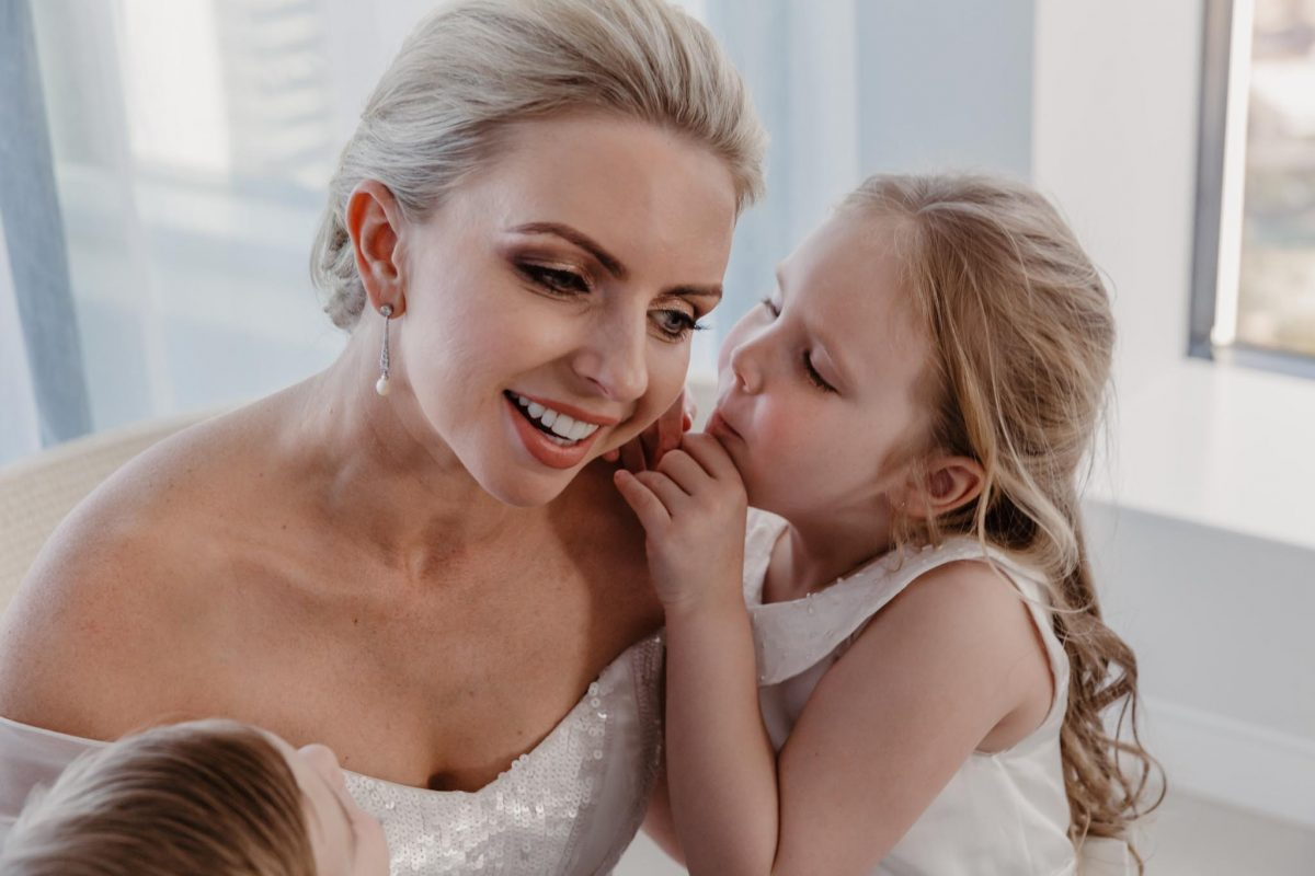 Preparing-to-walk-down-the-aisle-on-her-wedding-day-this-stunning-bride-is-given-last-minute-kisses-and-cuddles-from-her-beautiful-children-gold-coast-family-documentary-wedding-photography