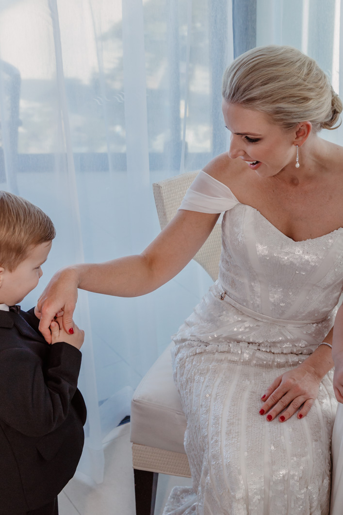 Page-image-young-son-kissing-the-hand-of-his-mum-on-her-wedding-day-dressed-and-ready-to-walk-down-the-aisle-gold-coast-family-documentary-photography