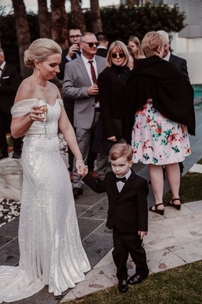 page-image-a-beautiful-bride-takes-the-hand-of-her-toddler-son-and-provides-comfort-during-the reception-of-her-wedding-beautiful-intimate-mother-and-son-moment-gold-coast-family-documentary-wedding-photography