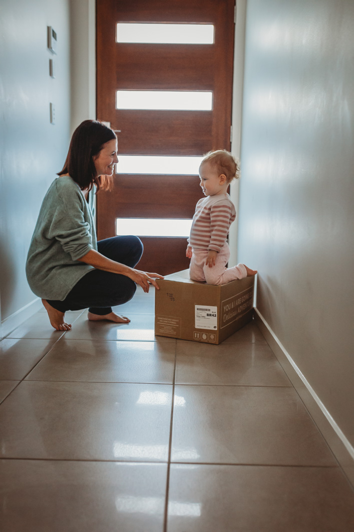 mum-and-baby-in-hallway-playing-with-cardboard-box-baby-is-very-amused-gold-coast-family-photography