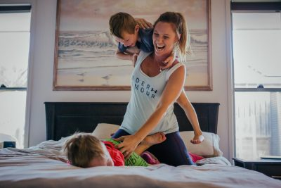 Two-kids-jumping-on-the-bed-with-mum-in-front-of-painting-that-was-their-grandmas-part-of-a-remembering-mum-series-gold-coast-australia-family-documentary-photography