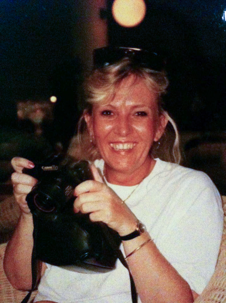 Carol_Weber-holding-camera-with-huge-smile-Flame-of-a-woman