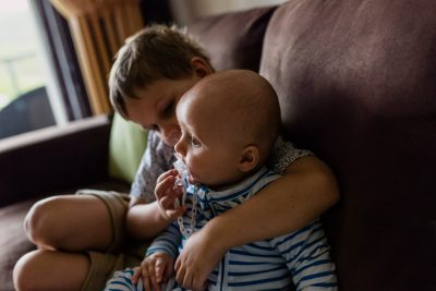 little-boy-giving-his baby-cousin-his-dummy-whilst-hanging-on-the-couch-together-as-part-of-a-holiday-family-documentary-photography-session-gold-coast