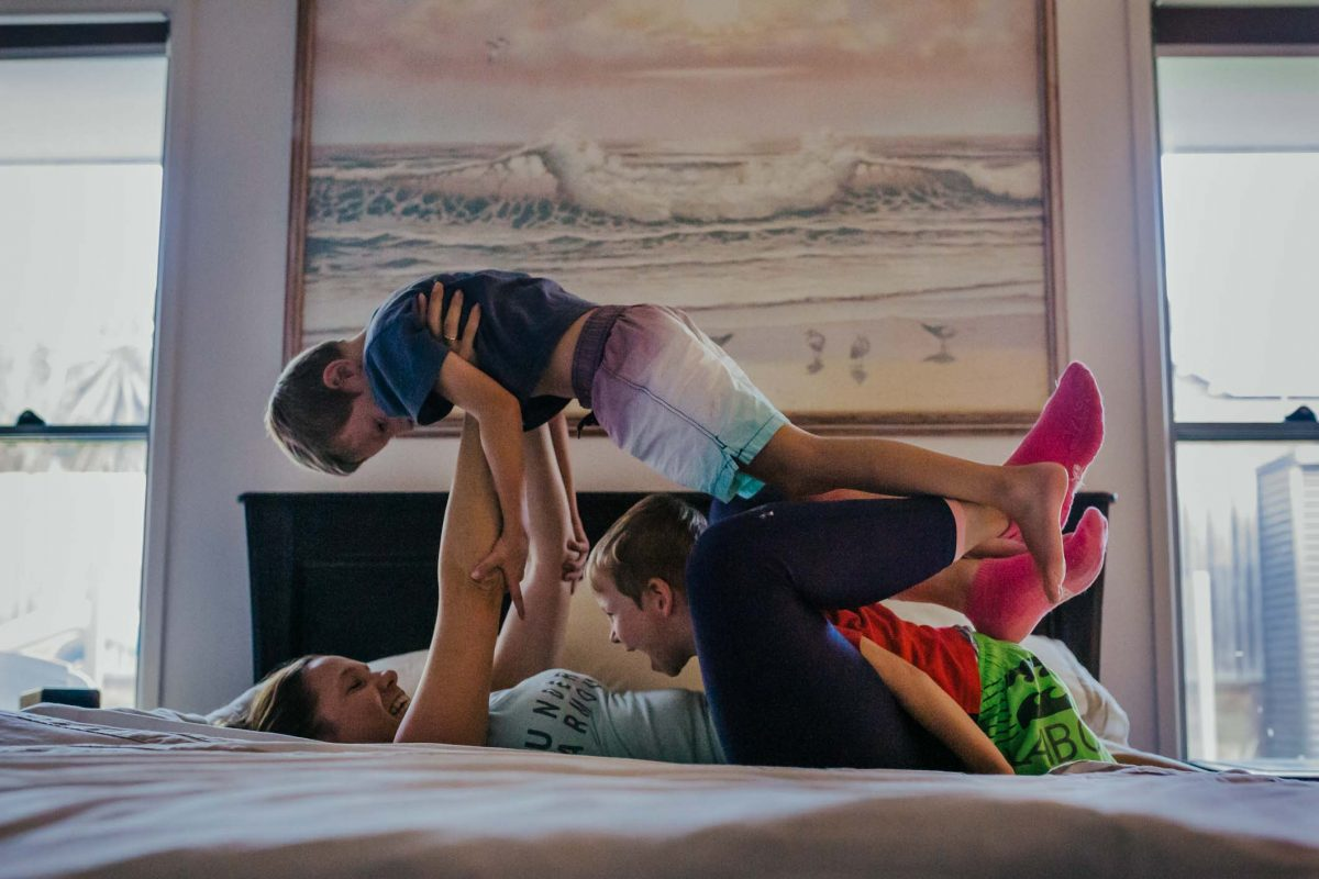 blog-image-Two-kids-jumping-on-the-bed-with-mum-in-front-of-painting-that-was-their-grandmas-part-of-a-remembering-mum-series-gold-coast-australia-family-documentary-photography
