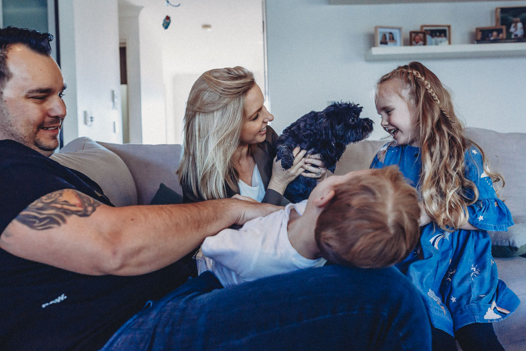 Family-playing-on-couch-and-puppy-joins-in-and-licks-little-girls-face