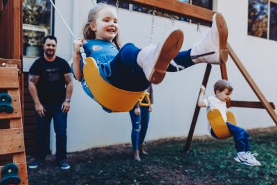 Girl-being-pushed-on-swing-at-home-as-part-of-family-short-story-telling-photography-session