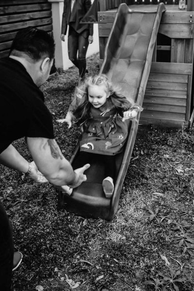 young-girl-coming-down-slide-into-the-strong-hands-of-her-dad-gold-coast-family-short-story-telling-photography