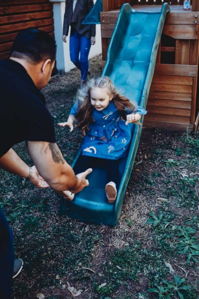 young-girl-coming-down-slide-into-the-strong-hands-of-her-dad-gold-coast-family-short-story-telling-photography-in-colour