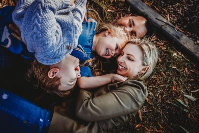 a-family-having-a-cuddle-puddle-on-the-ground-at-the-park,laughing-and-giggling-as-part-of-their-gold-coast-family-short-story-telling-photography-sessio
