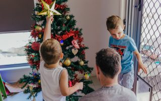 Young-boy-holding-up-the-xmas-tree-star-surrounded-by-his-dad-and-brother-as-they-work-to-decorate-the-tree