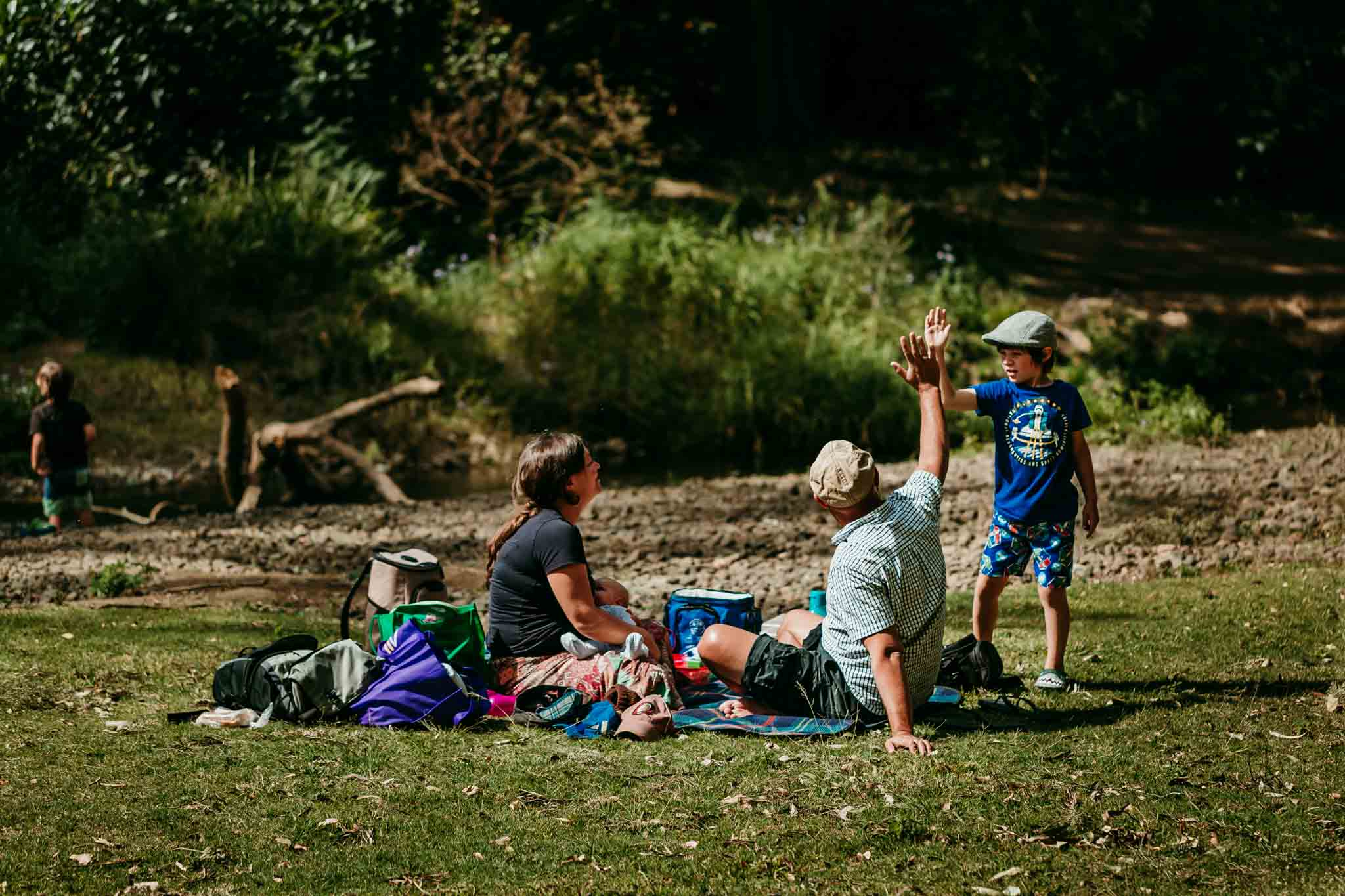 Family-enjoying-a-picnic-with-toddler-high-fiving-dad-after-crossing-the-Canungra-creek