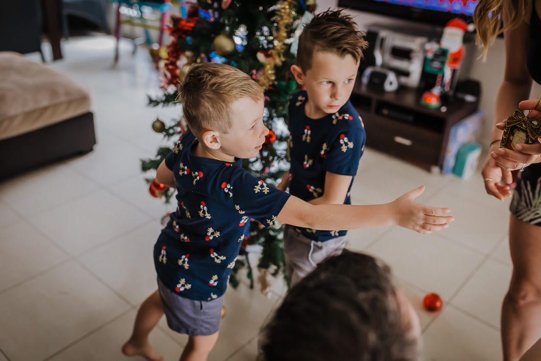 Brothers reaching out to their mum to pass them the Christmas ornament that features a picture of their grandma