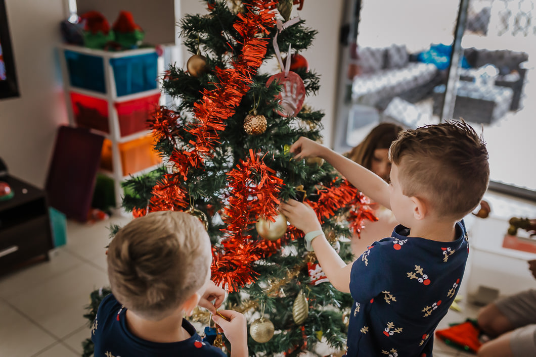 Boys decorating their Christmas tree as part of a documentary family photography session