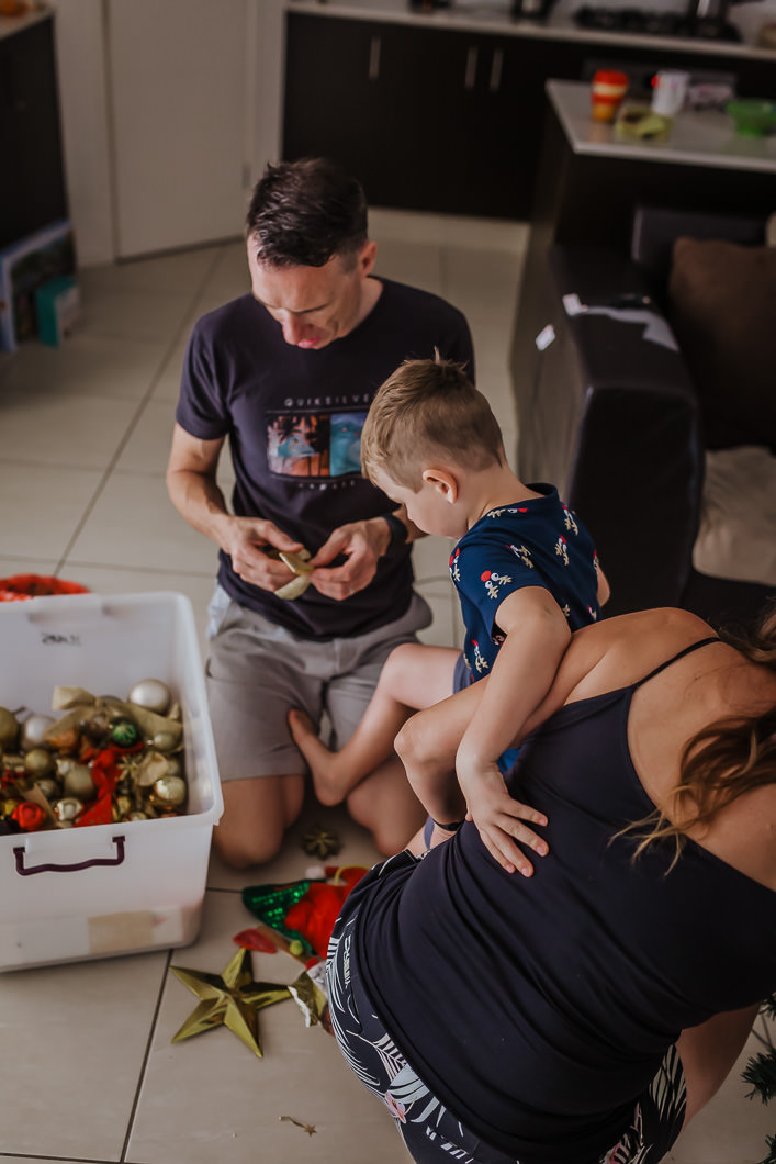 a young boy climbing over his mum to grab a Christmas ornament to hang on the tree as part of a Gold Coast family photography session