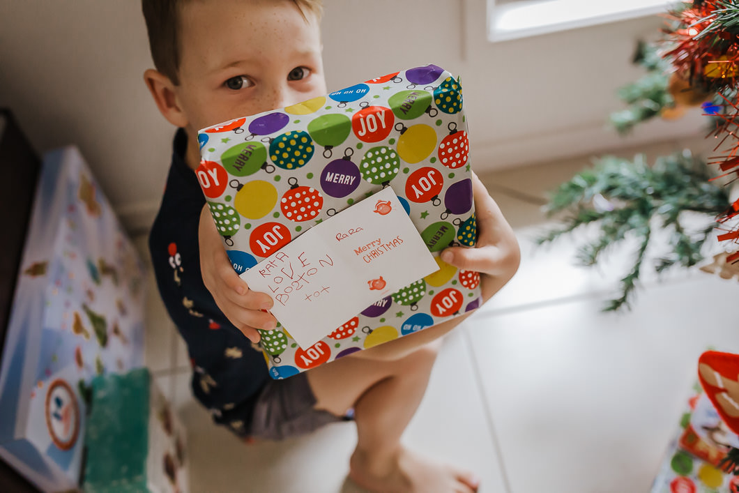 child showing his writing on a Christmas card for his aunty and placing the present under the tree