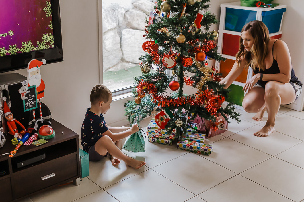 children feeling the Christmas presents as they place them under the tree