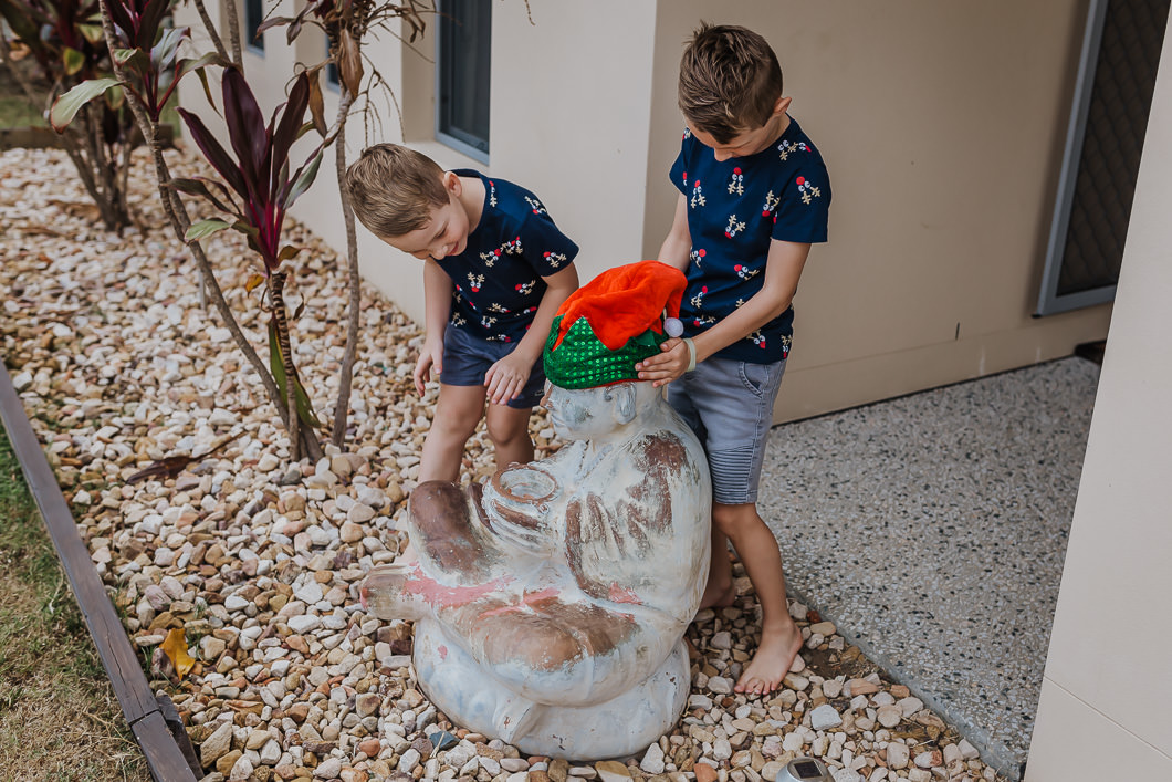 children dressing their buddha statue in xmas hat