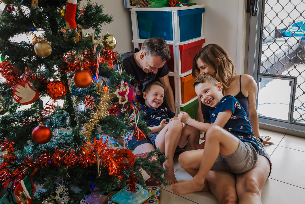 sweet family sitting by their Christmas tree having a cuddle with the kids as they excitedly look on over their Christmas tree