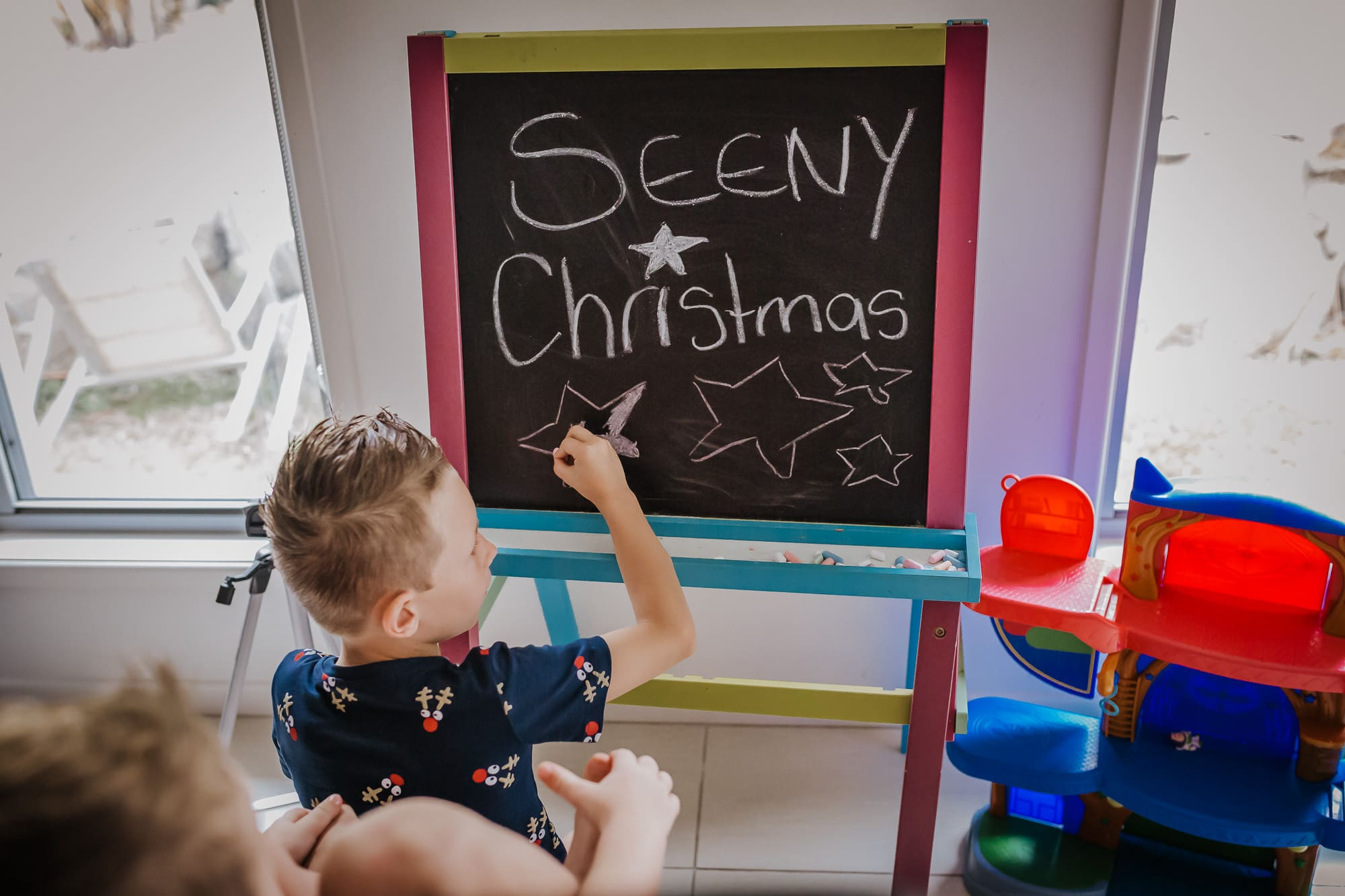 boy writing Seeny Christmas on blackboard before the family start putting up the xmas tree as part of a limited edition Christmas traditions family photography session