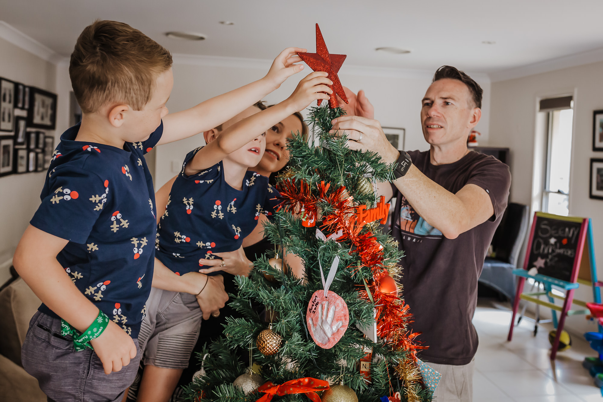 mum dad and their two sons putting the star on top of the Christmas tree