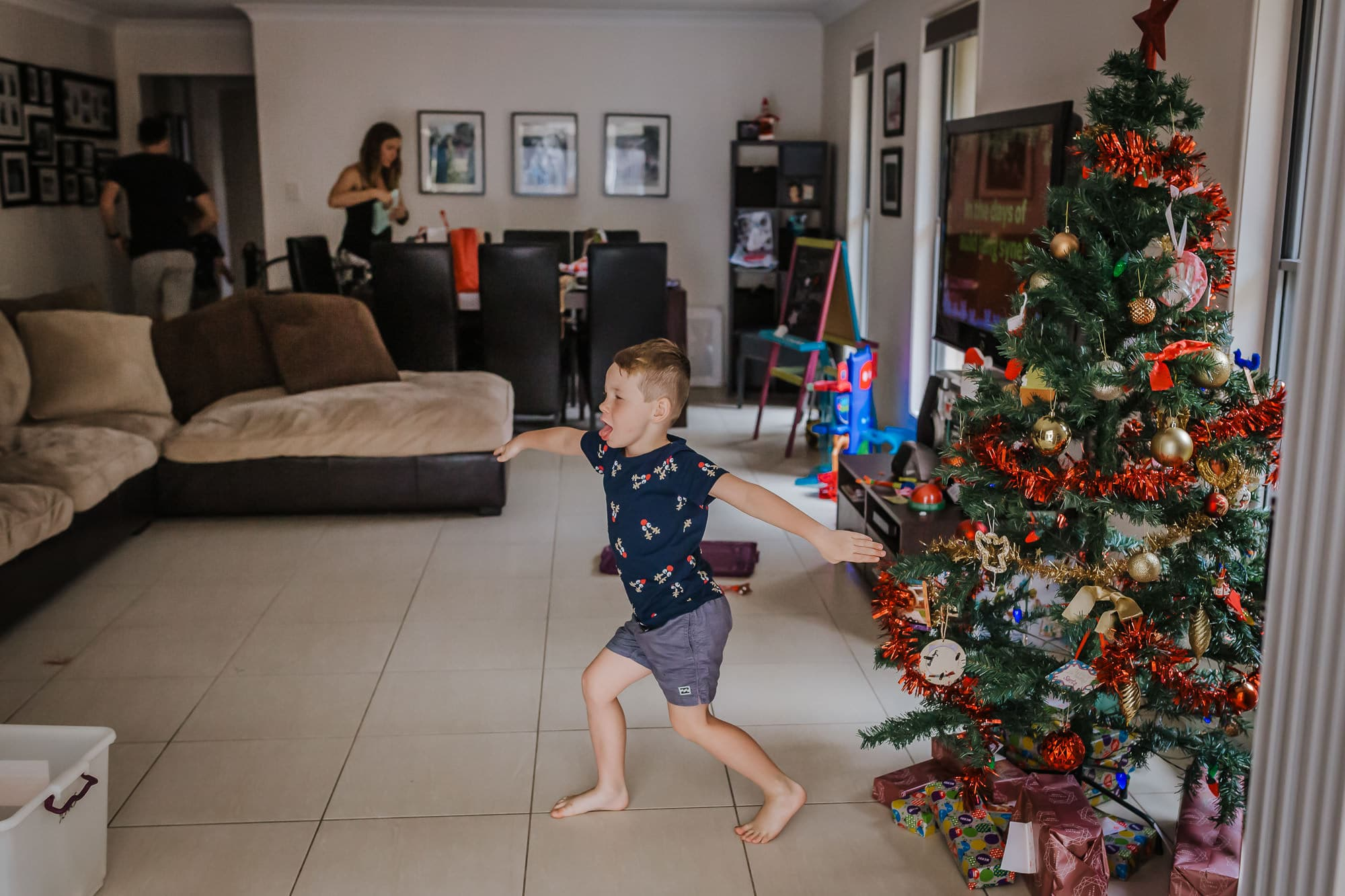 four year old son has a little dance moment as the family finish putting up the Christmas tree and placing all the present underneath